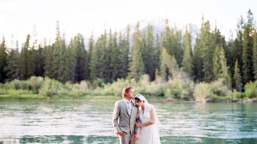 Canmore elopement - beautiful bride and groom standing in front of Bow River and mountains in the background.